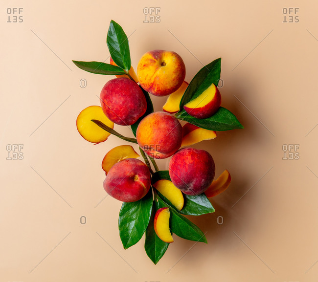 Group of peaches with leaves on a tan background