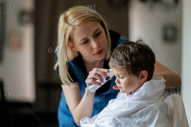 Mother cutting her son's hair at home during self-isolation and pandemic