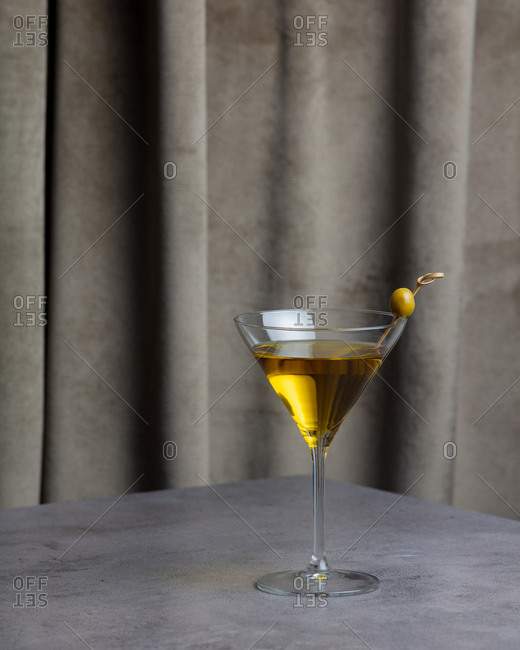 Yellow colored vodka with olive on a table