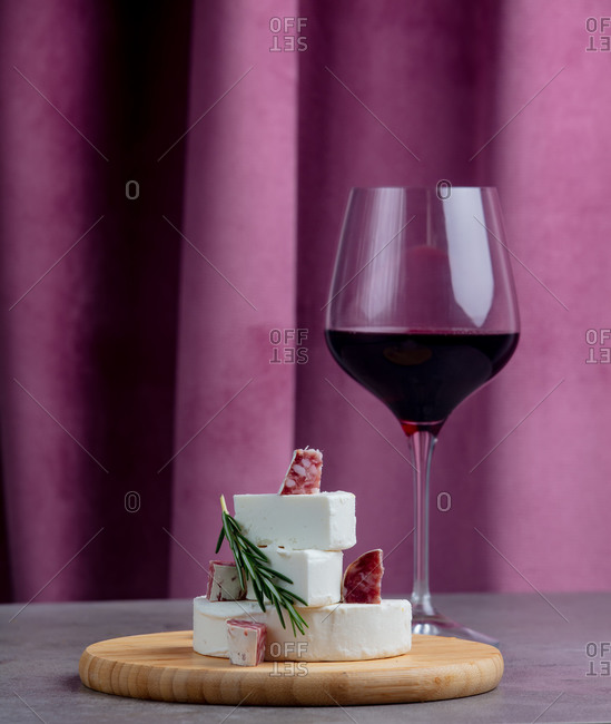 Glass of wine and white goat cheese with sausage