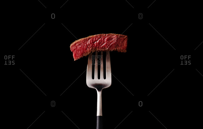 Close-up image of beef medium rare steak slice on a fork on dark background
