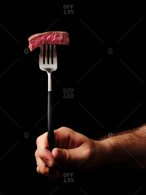 Male hand holding a fork with a slice of beef medium rare steak on it