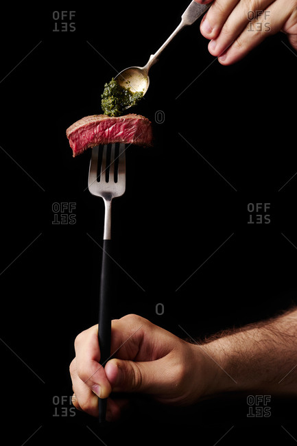 Male hand holding a fork with a slice of beef medium rare steak and putting sauce on it