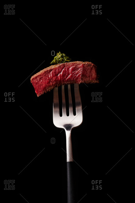Close-up image of beef medium rare steak slice on a fork with herb butter