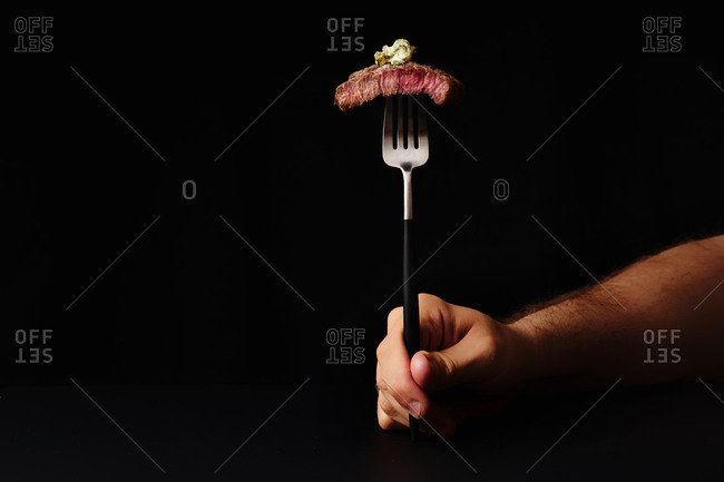 Male hand holding a fork with a slice of beef medium rare steak served with herb butter on it