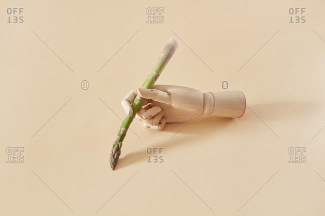 Wooden mannequin hand is writing by natural organic asparagus spear as a pan on a sand yellow background, copy space.