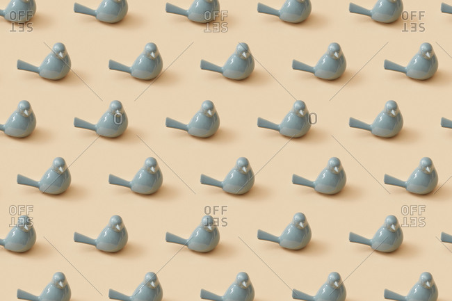 Decorative pattern from small grey porcelain birds for interior on a sand yellow background. Interior decoration concept.