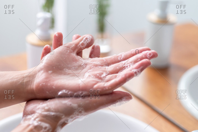 Detail of Woman's hands using soap and washing hands under the water tap