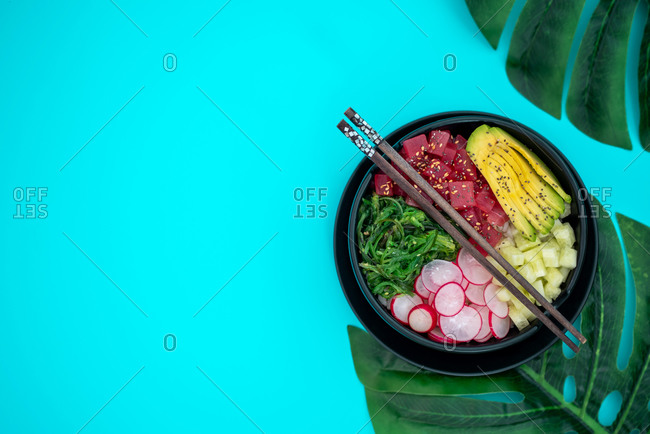 Top view of tuna poke bowl with rice, avocado, wakame, radish and cucumber on blue background