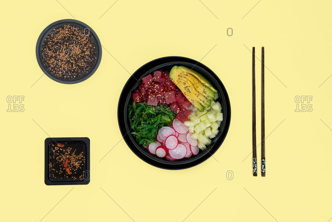 Top view of tuna poke bowl with rice, avocado, wakame, radish and cucumber on yellow background