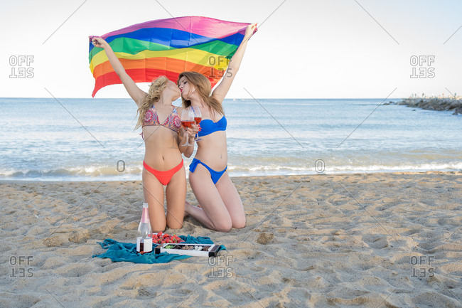 Slim girlfriends with glasses of wine and LGBT flag kissing each other during picnic on sandy beach near waving sea