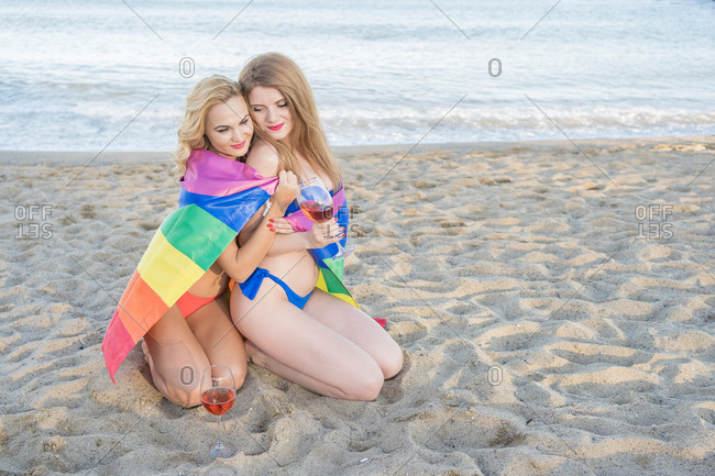 Lesbian couple wrapped in LGBT flag smiling and enjoying wine while resting on sandy beach during date