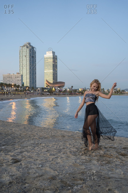 Side view of female in top and transparent skirt walking on sandy beach near sea in Barcelona
