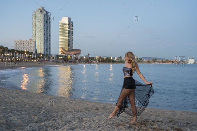 Side view of female in top and transparent skirt walking on sandy beach near sea in evening in Barcelona