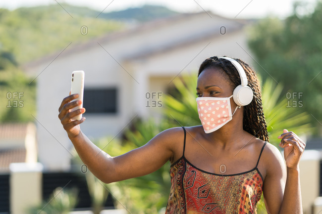 Beautiful woman with dark curly hair and mask taking selfie with her cell phone sitting in the garden wearing a mask