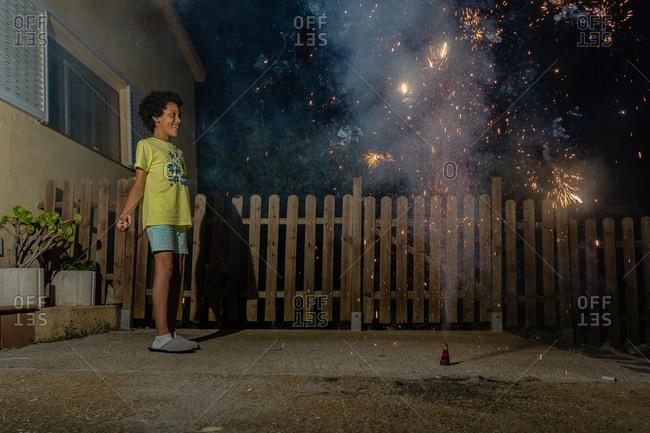 Black boy with curly hair watching backyard fireworks