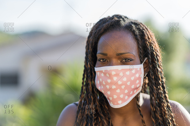 Portrait of an African-American woman with afro hair and protective mask