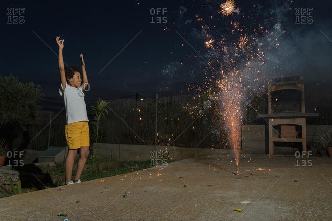Young Black boy with curly hair enjoying backyard fireworks