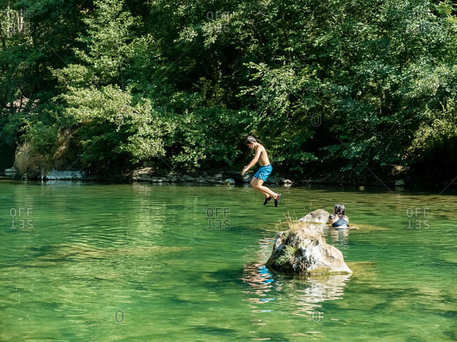 Carefree shirtless boy jumping in river from a rock