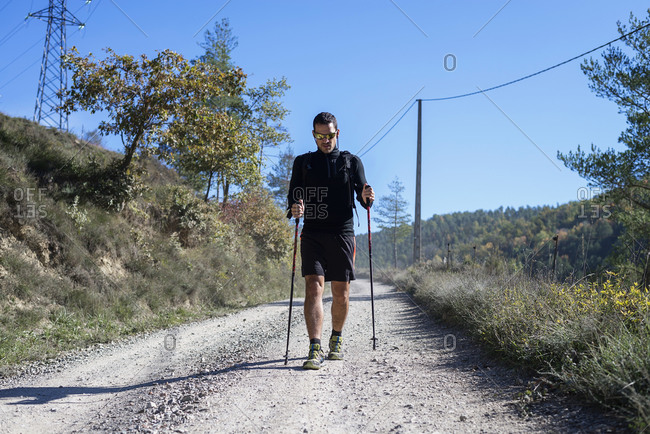 Front view of a hiker walking with trekking poles