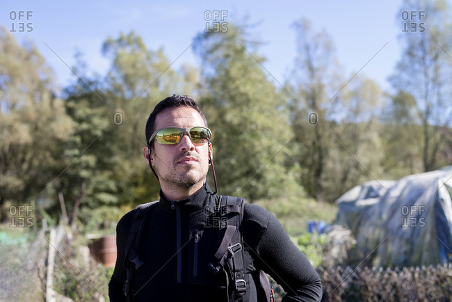 Portrait of adult bearded male in hiking sunglasses looking around walking in forest