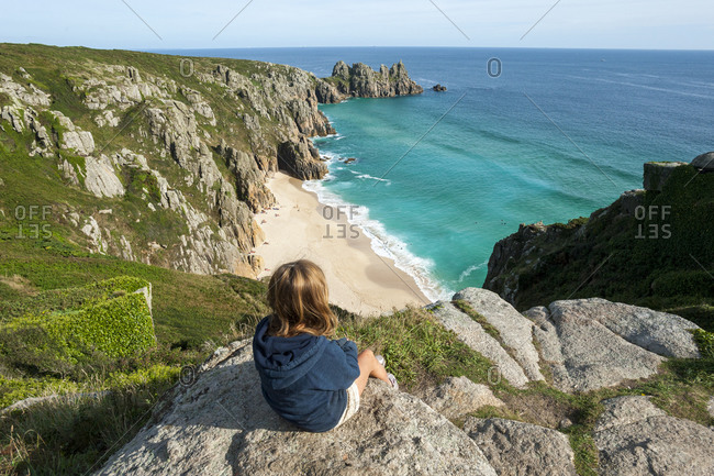 A little girl looks down on Treen beach in Cornwall the westernmost part of the British Isles