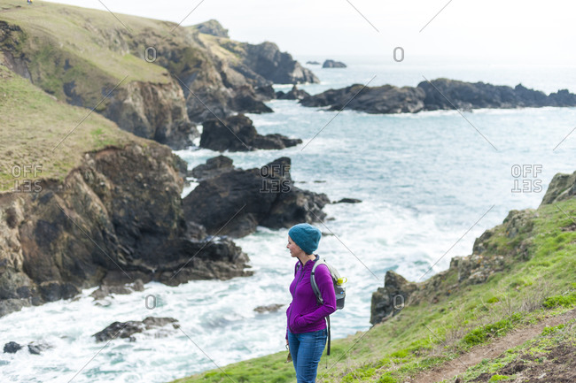 A woman looks out over dramatic Cornish coastline on the Lizard
