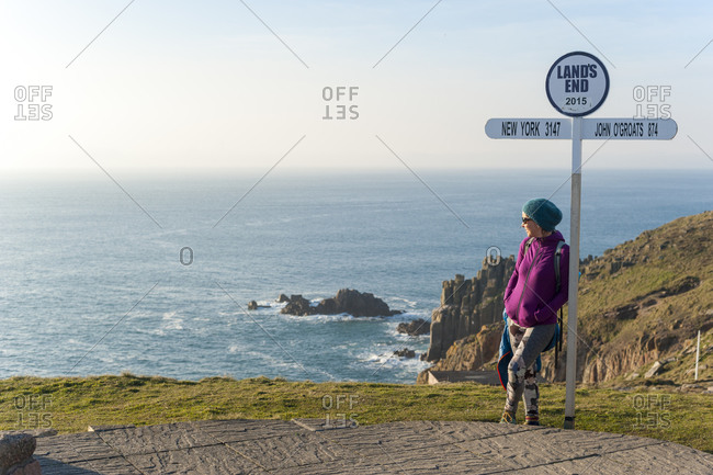 A woman looks out over dramatic Cornish coastline at Land's End at the westernmost part of the British Isles