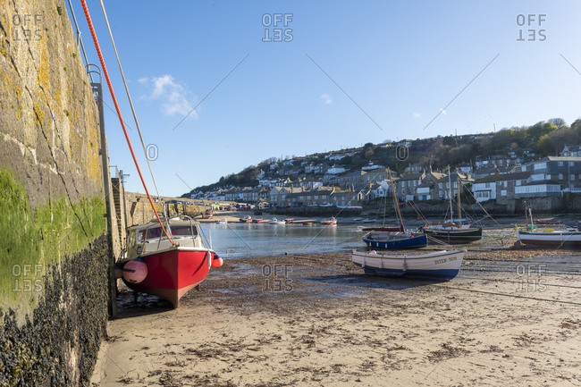 Mousehole, Cornwall, United Kingdom - April 22, 2018: Boats moored in the harbour at Mousehole in Cornwall