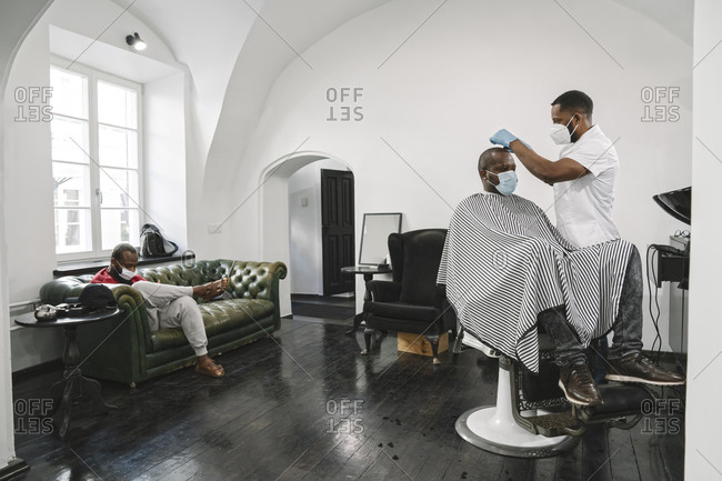 Barber wearing surgical mask and reusable gloves cutting hair of the customer