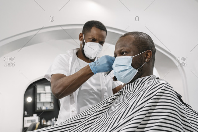 Barber wearing surgical mask and gloves cutting hair of customer