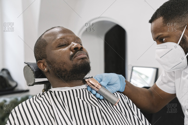 Barber wearing surgical mask and gloves cutting beard of customer