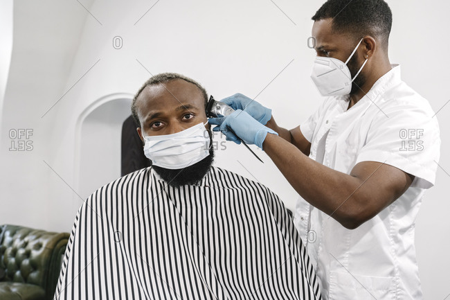 Barber wearing surgical mask and reusable gloves shaving hair of customer