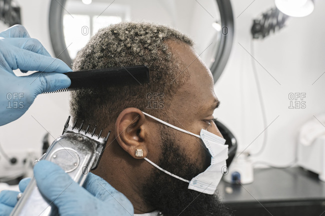 Barber wearing surgical mask and gloves doing hair of customer