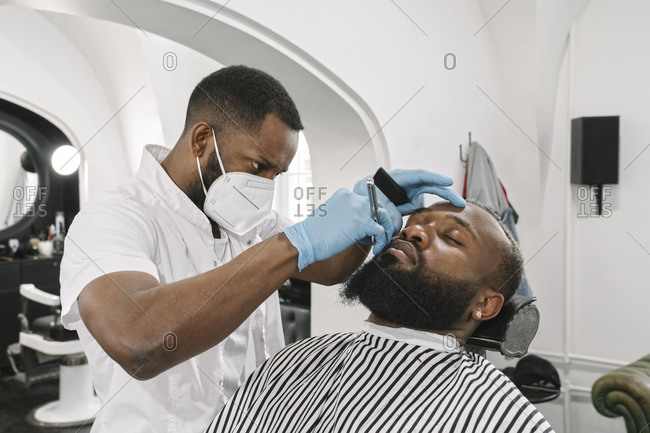 Man with full beard getting a shave- barber wearing surgical mask and gloves