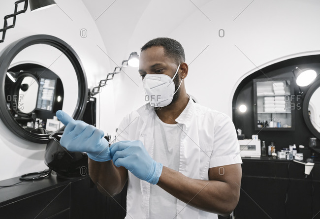 Barber wearing surgical mask putting on reusable gloves