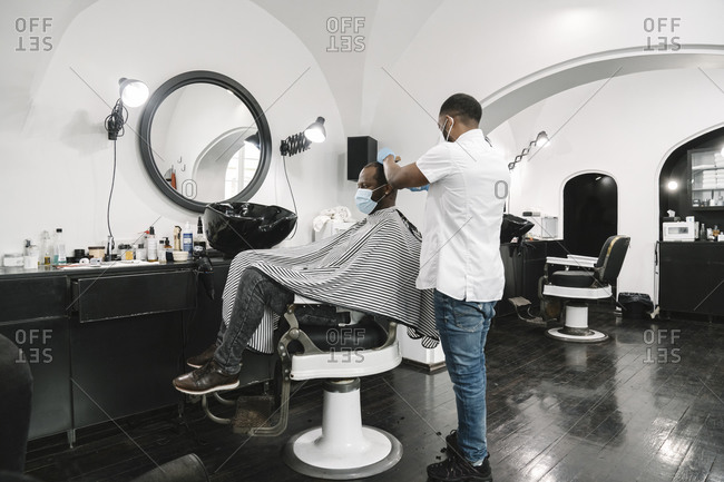 Lithuania- Vilnius- Barber wearing surgical mask and gloves cutting hair of customer