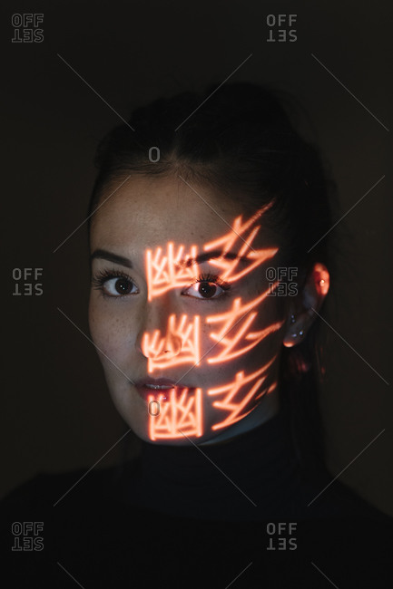 Face of beautiful woman covered in light patterns