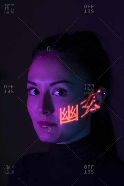 Headshot of woman with light pattern on her cheek