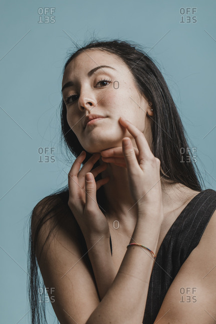 Beautiful woman touching her face in front of green background