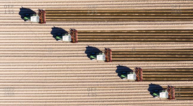Germany- Hesse- Bergstarsse- Aerial view of tractors plowing brown field in spring