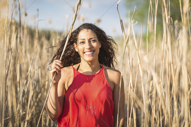 Portrait of happy young woman  among reed
