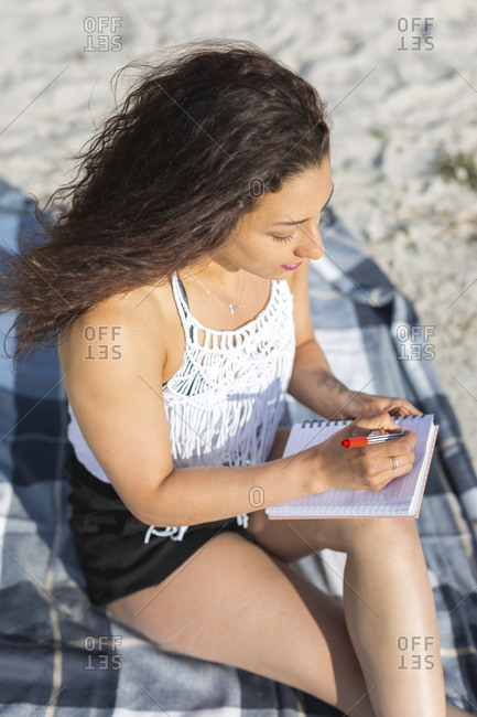 Young woman sitting on blanket on the beach writing in notebook
