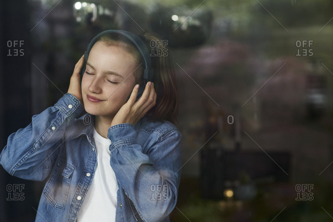 Pre-adolescent girl with eyes closed enjoying music listening through headphones at home
