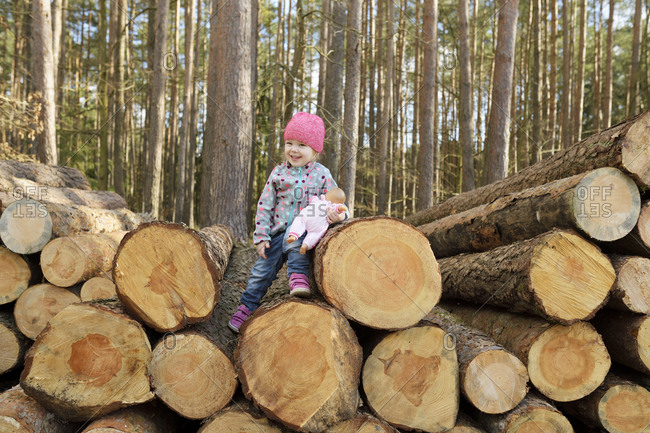 Smiling little girl with doll sitting on stack of wood in the forest