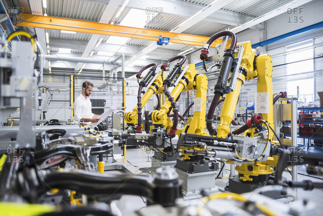 Young engineer reading paper while standing by robotic arms in automated industry