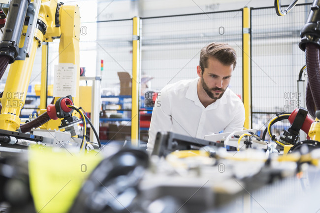 Confident young male engineer examining automated machinery in robotic factory