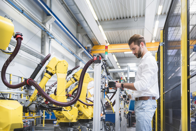 Side view of confident robotics expert examining machinery in factory