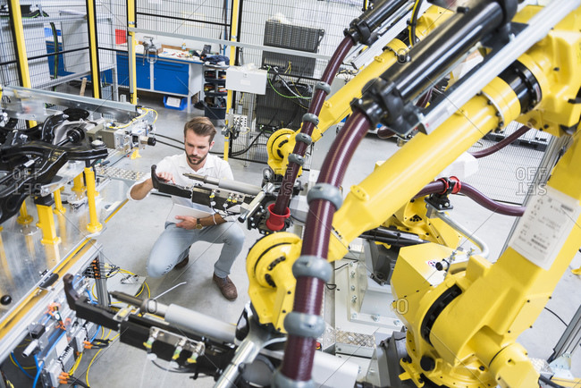 Full length of young engineer crouching while examining computer-aided machinery in automated industry