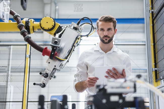 Young robotics engineer looking away while standing by machinery in factory